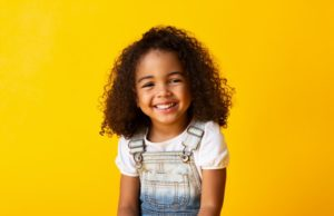 a little girl wearing overalls and smiling